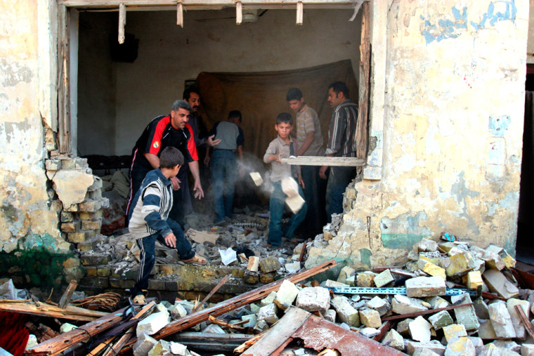 Iraqi men sweep up debris of their damaged house on Sunday after some of the violence that punctuated the weekend in Baghdad.