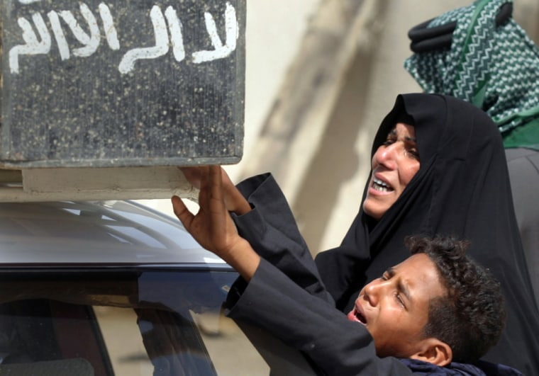 Woman and boy reach out to touch coffin of youth killed by blast in southern Iraqi city of Basra