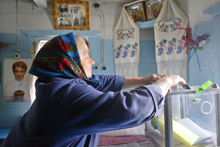 A woman casts her ballot at her home in