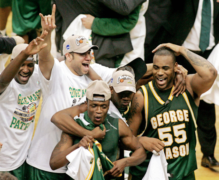 George Mason University's Lewis and Skinn celebrate with teammates after defeating the University of Connecticut in Washington