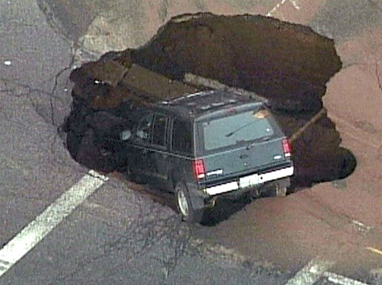 The SUV rests in the Brooklyn street sinkhole.