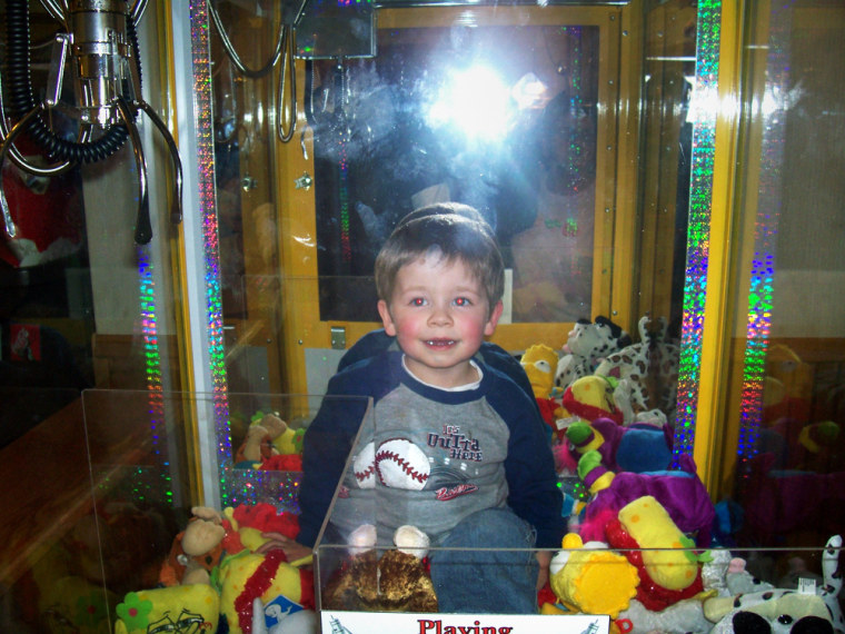 Devin Haskin, 3, plays inside the Toy Chest claw machine at Godfather's Pizza on Sunday in Austin, Minn., after crawling through the toy discharge chute.