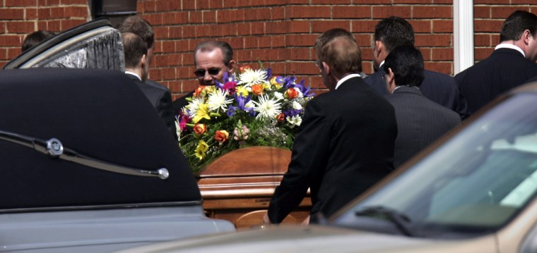 Pall bearers remove the casket bearing the body of pastor Matthew Winkler from the hearse to carry it into the church for his funeral service in Selmer, Tenn. on Tuesday.