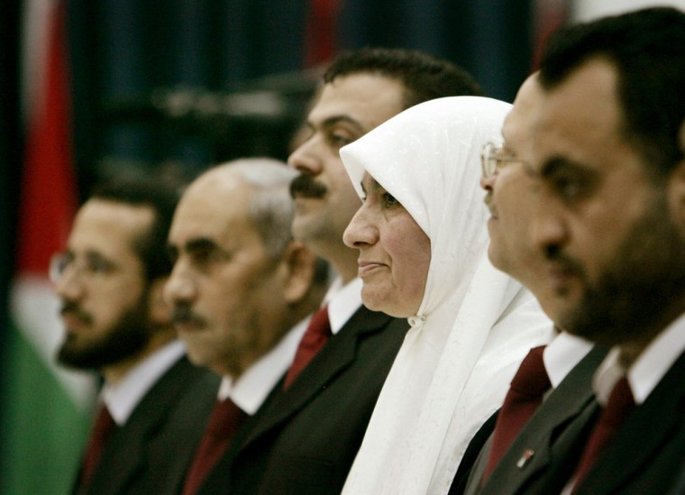 Dr. Mariam Saleh, center, the only womanin the new Palestinian government, is sworn in along withother members of the Hamas cabinet inRamallahon Wednesday.