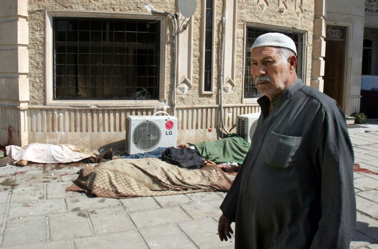 An Iraqi man walks past the bodies of the employees of a trading company after an attack that killed eight Wednesday in Baghdad.