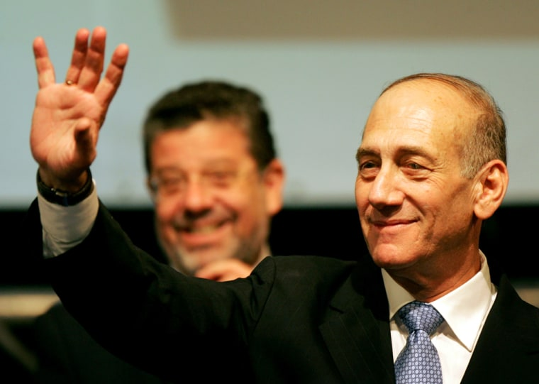 Israeli interim Prime Minister Ehud Olmert waves after early exit polls in Israel