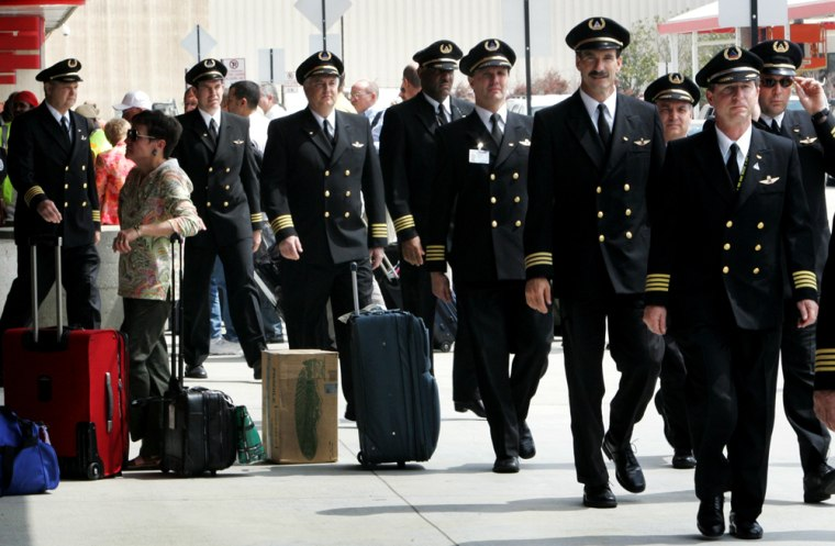 Delta pilots walk past a baggage check area ouside Hartsfield-Jackson International Airport in Atlanta on Thursday. About 275 Delta pilots marched through the Atlanta airport to protest proposed concessions.