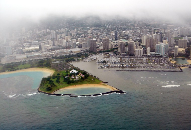 Water darkened by raw sewage pours out of the Ala Wai Canal and harbor areain Honolulu on Wednesday.