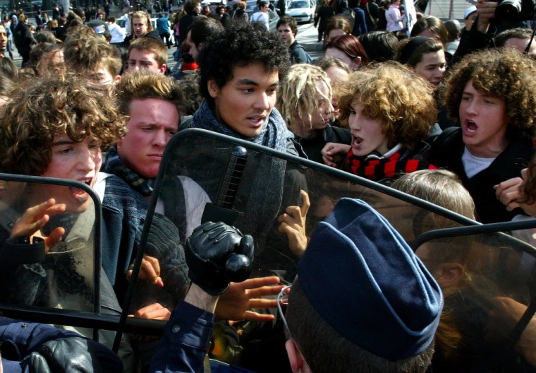 French police hold students back during a protest against the youth job law in Paris