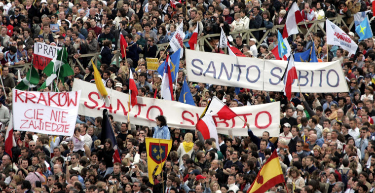 Members of the crowd hold banners calling for 'Santo Subito' - 'Sainthood now'' for Pope John Paul II, during his funeral mass in St.Peter's Square at the Vatican, omApril 8, 2005.