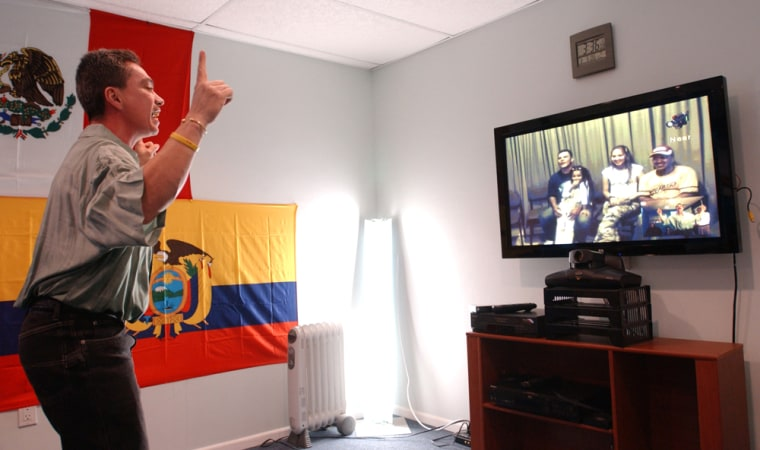 Mario Melan stands up in front of the camera to show that he has managed to stay in shape while living in New York as he communicates with his family in Medellin, Colombia, at a video conferencing center in Bayshore, N.Y., earlier this month.