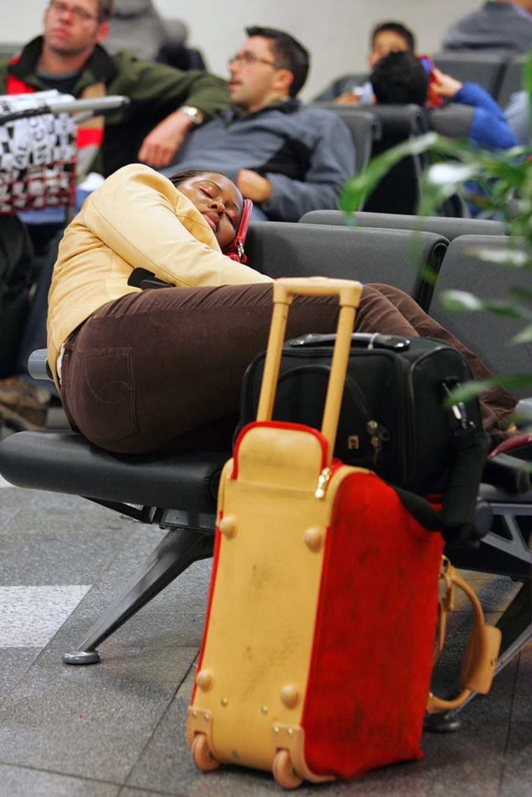 A woman sleeps beside her luggage inside New York's LaGuardia Airport