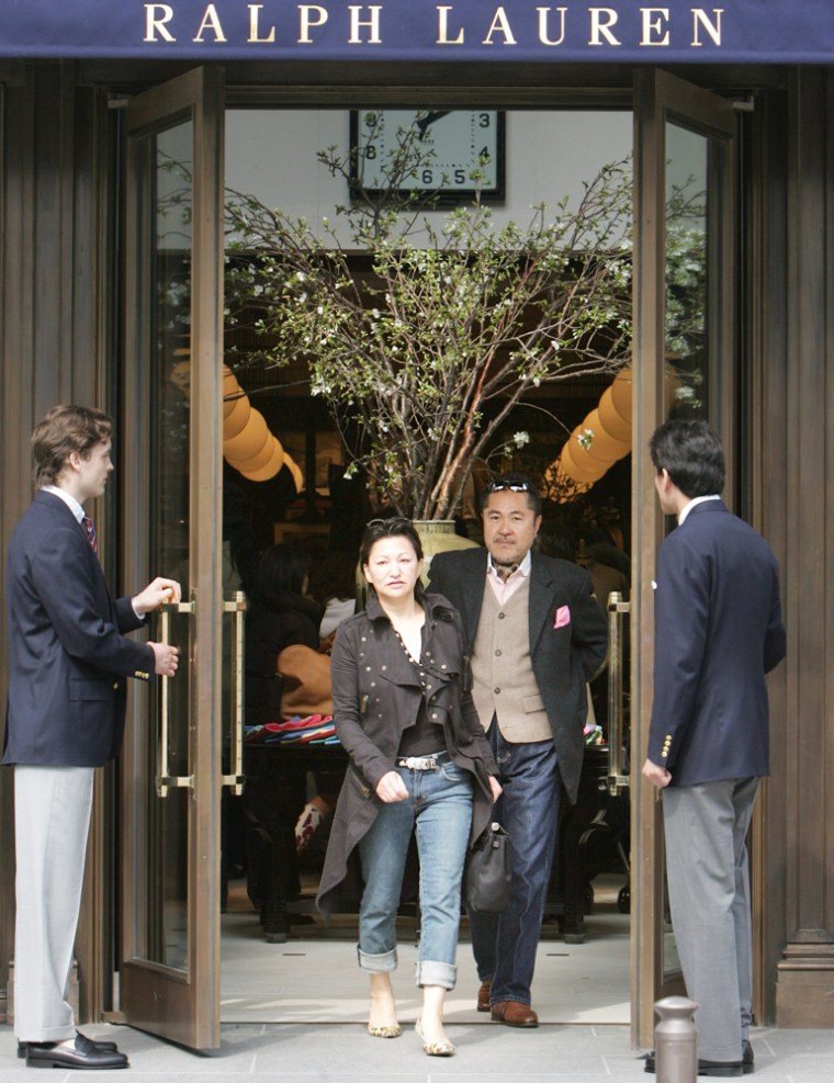 A Japanese couple leaves a newly opened Ralph Lauren store on a glitzy Tokyo street on March 30. Meanwhile, the number of Japanese living below the poverty level is growing.