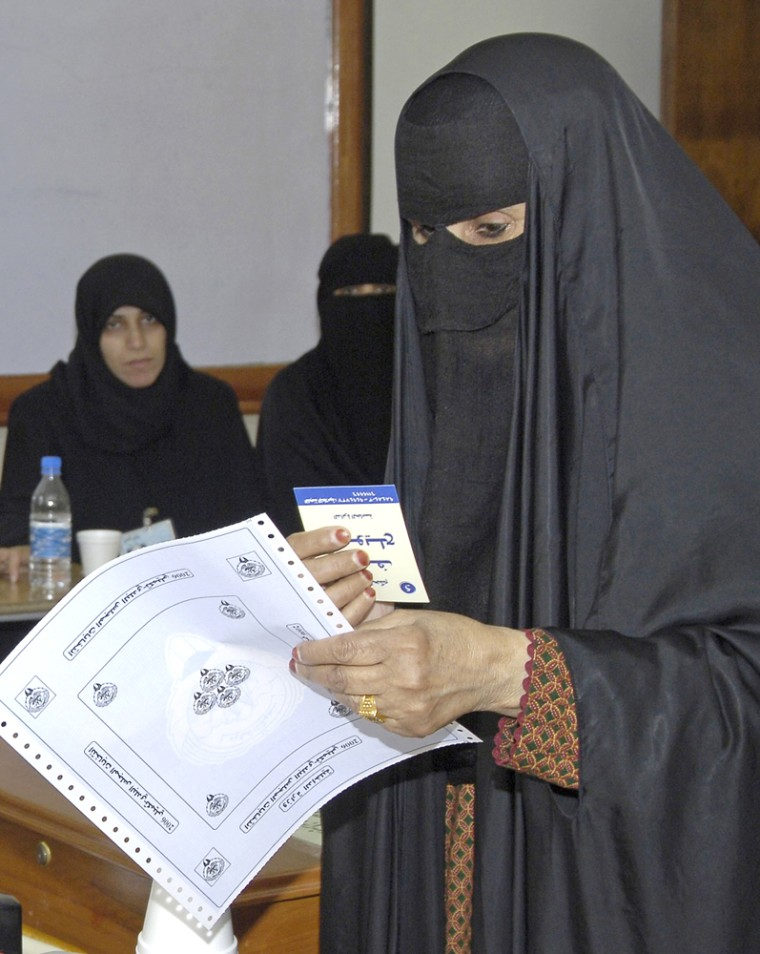 A Kuwaiti woman casts her ballot for a single municipal council election at a polling station in Rourmaithiya