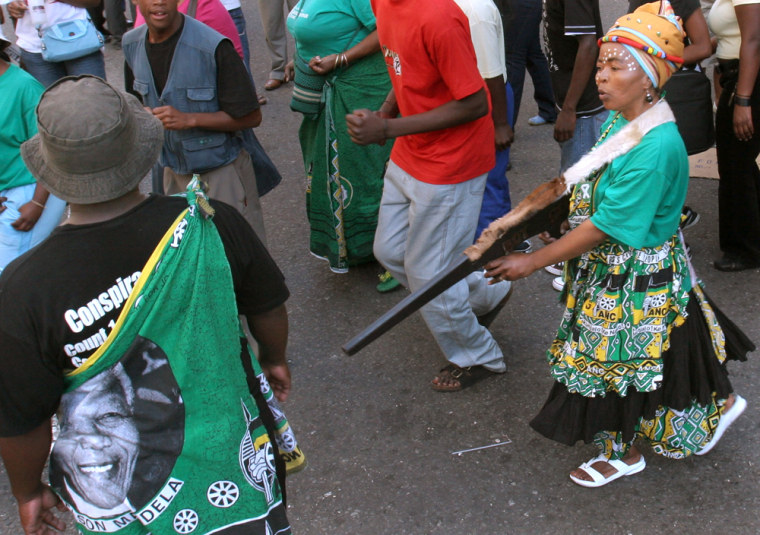 A woman pretending to fire a mock weapon joins supporters of former deputy president Jacob Zuma in protest outside the High Court in Johannesburg on Wednesday, April 5, 2006. In Zuma's ongoing rape trial he told the court that he took a shower to reduce the risk of infection after unprotected sex with an HIV-positive woman.
