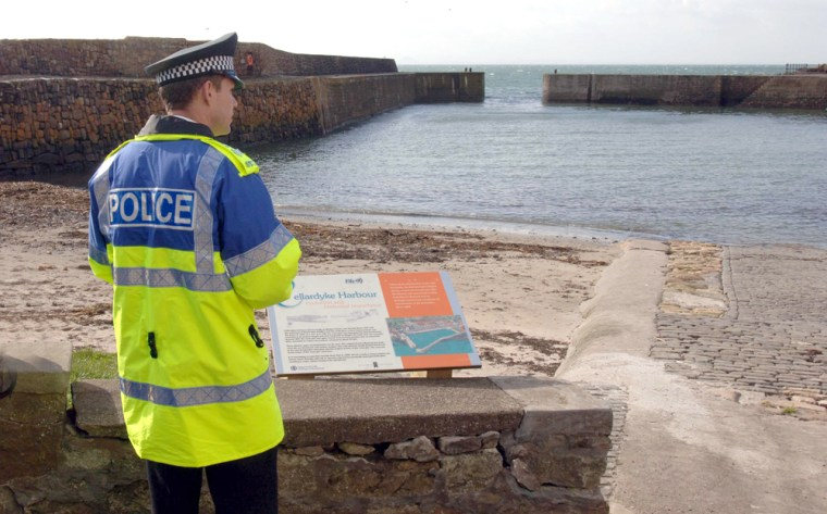 A policeman looks out over the harbour of Cellardyke on the east coast of Scotland 450 milesnorth of London onApril 6.