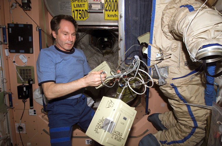 "Russian cosmonaut Valery Tokarev puts the finishing touches on an old Russian spacesuit that was released from the international space station as a ""SuitSat"" amateur-radio satellite during a February spacewalk."