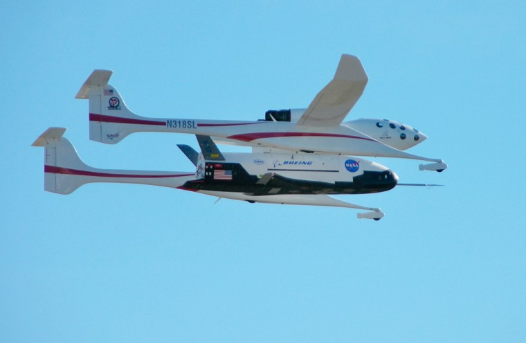 The X-37 space plane is tucked beneath its White Knight mothership during a test flight this week. At the climax of a similar flight on Friday, the X-37 was released for a drop testand landed autonomously, but ran off the runway.