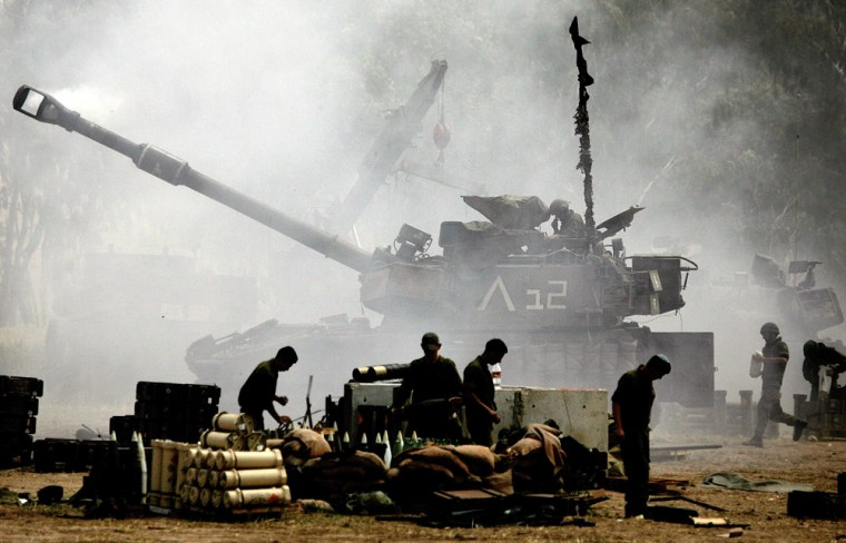 Israeli soldiers prepare to reload an Israeli mobile artillery piece Sunday, as it fires toward the Gaza Strip, at a position near the southern Israeli Kibbutz Nahal Oz.