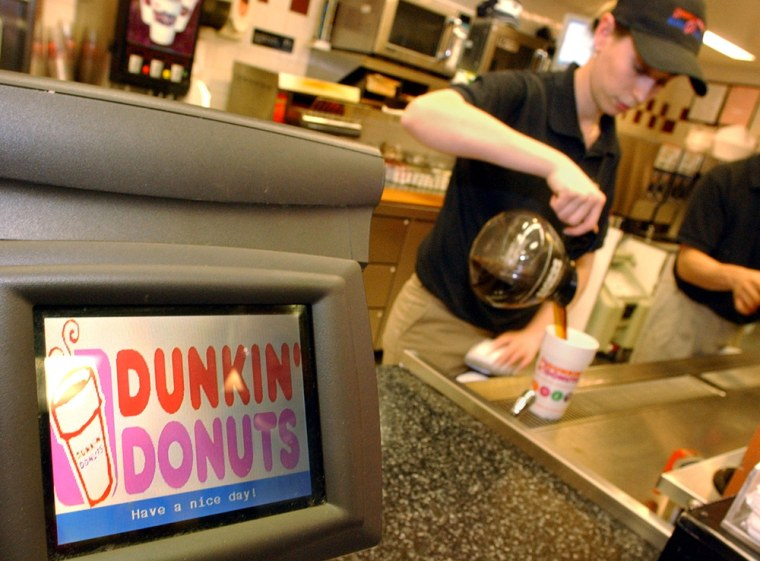 """Dunkin' Donuts employee Sandra Manoel pours coffee for a customer in Cambridge, Mass. The company's new advertising campaign is called """"America Runs on Dunkin."""""""