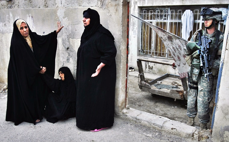 A U.S. Army soldier stands guard while women cry after soldiers kickeddown their front gate Thursday in the Shula section of Baghdad, Iraq.