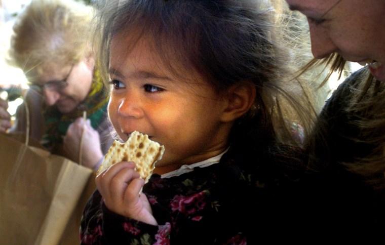 Tatiana Isabella, 22 months, with Laura Holman, samples Matzoh at Whole Foods Market in Arlington, Va.