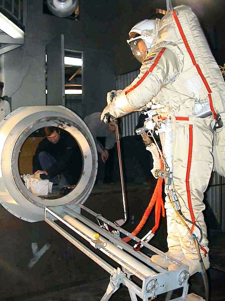 Russian cosmonaut Pavel Vinogradov practices hitting a golf ball in his bulky spacesuit at the Star City training complex outside Moscow inthis 2005 photo provided by Element 21 Golf, the manufacturer paying for the golf stunt.