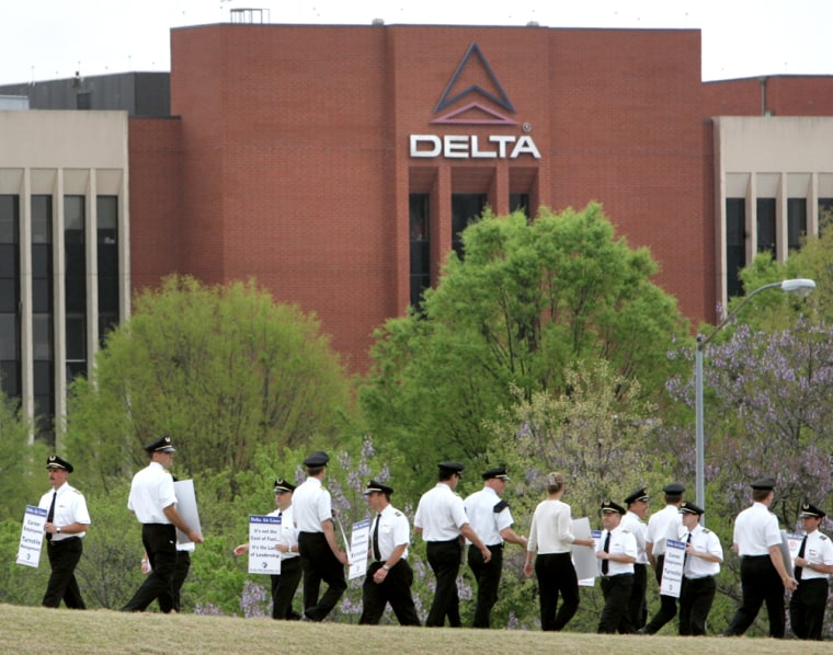 Delta Air Lines pilots walk a picket line near their headquarters on Wednesday. The airline and its pilots union reached a tenative deal that could avert a threatened strike, though it awaits approval from the flyers.