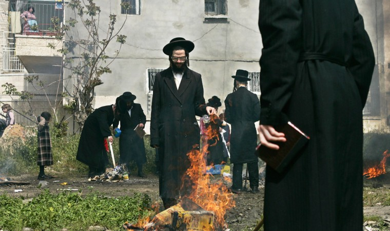 Orthodox Jews gather around a fire Wednesday as they burn leavened items in final preparation for Passover in Jerusalem. All leavened food such as bread is forbidden to Jews during the week-long holiday.