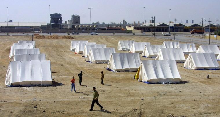 Iraqi Sunnis walk through lines of tents