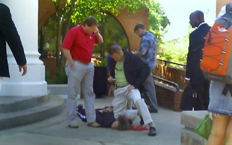 A photo taken with a student's camera phone shows a federal Bureau of Alcohol, Tobacco and Firearms official pinning down Jeremiah Ransom in front of Snelling dining hall Tuesday on the University of Georgia campus in Athens, Ga.