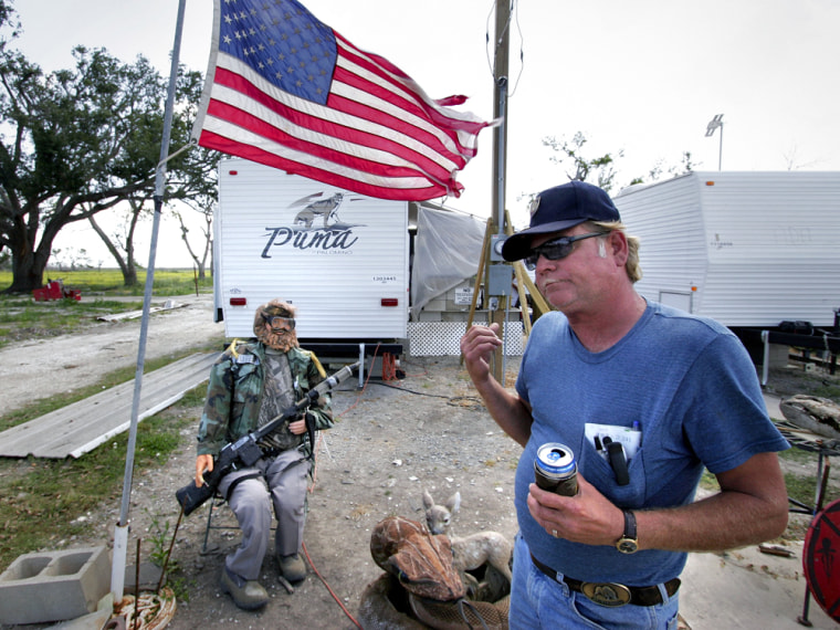 Chuck Bulotstands in front of adummy he and his friends made to guard their trailers in lower Plaquemines Parish, La., on Thursday.