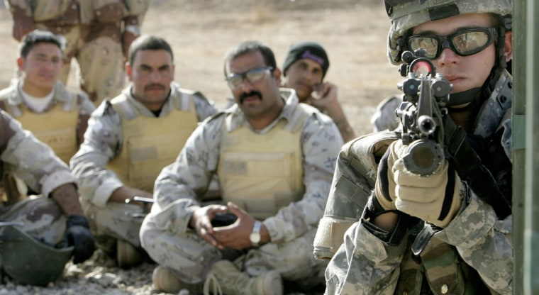 Iraqi soldiers look on as they are given