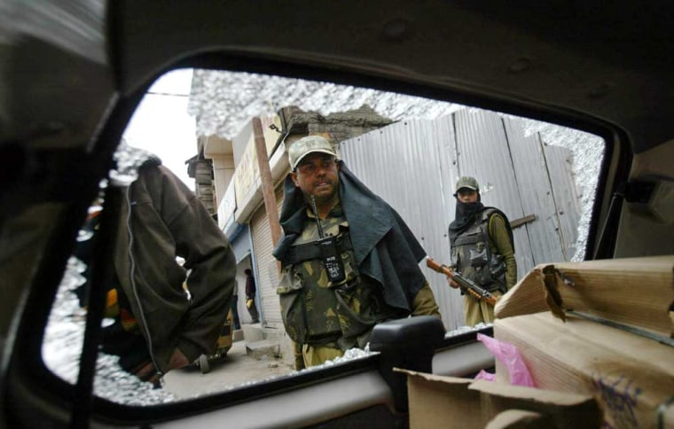 Paramilitary soldiers look at a vehicle damaged in a grenade explosion in Srinagar, India, Friday.