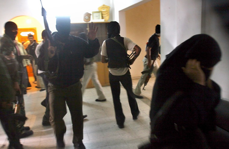 A female government worker, right, walks away as armed Palestinian policemen, some of them masked, take over a government building in the southern Gaza Strip town of Khan Younis on Saturday.