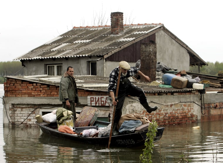 People remove items from a flooded home in the village of Oresac, near the Danube River, south of Belgrade on Sunday.