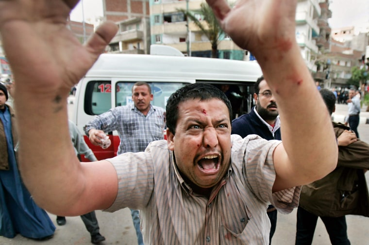 An injured Egyptian Coptic protester runs to an ambulance outside the St. Maximus Church in Alexandria, Egypt, onSunday.