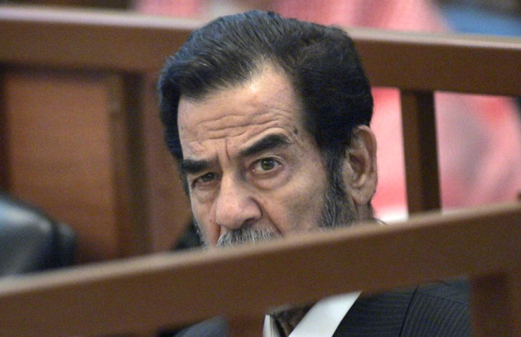 Former Iraqi President Saddam Hussein listens to chief Judge Raouf Abdel Rahman during trial in Baghdad