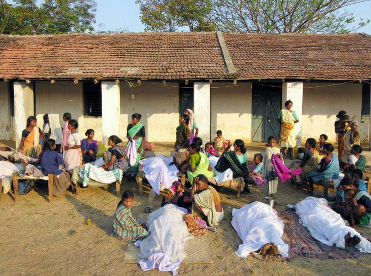 Relatives sit besides the dead bodies of those killed in a Maoist attack in Dharbaguda