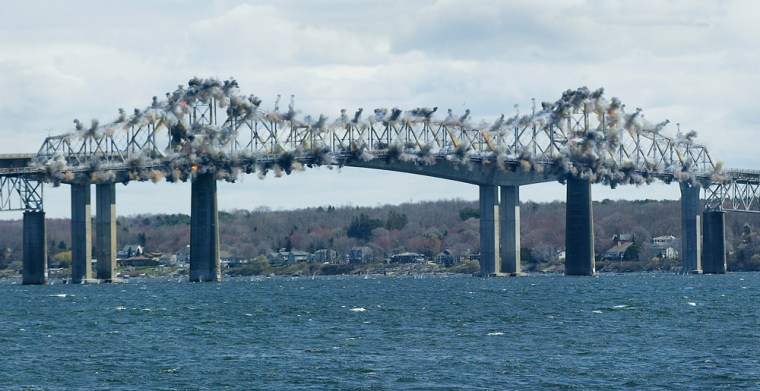 Explosives detonate along the 1100-foot steel center span of the old Jamestown Bridge on Tuesday in North Kingstown, R.I.