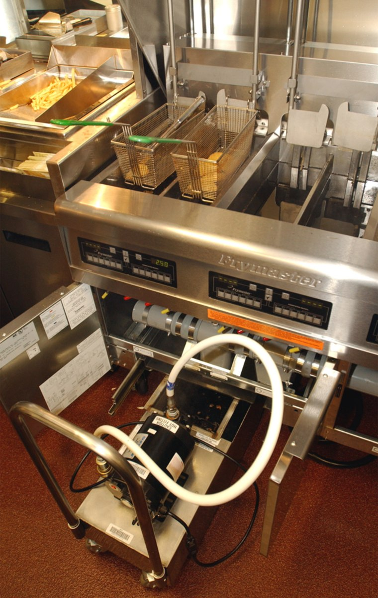 """Used cooking oil is drained from the fryers into a oil """"dog"""" or caddy at a Burgerville Restaurant in Salmon Creek, north of Vancouver, Wash. The restaurant has a state-of-the-art system for the recycling and pick-up of used cooking oil for biodiesel production."""