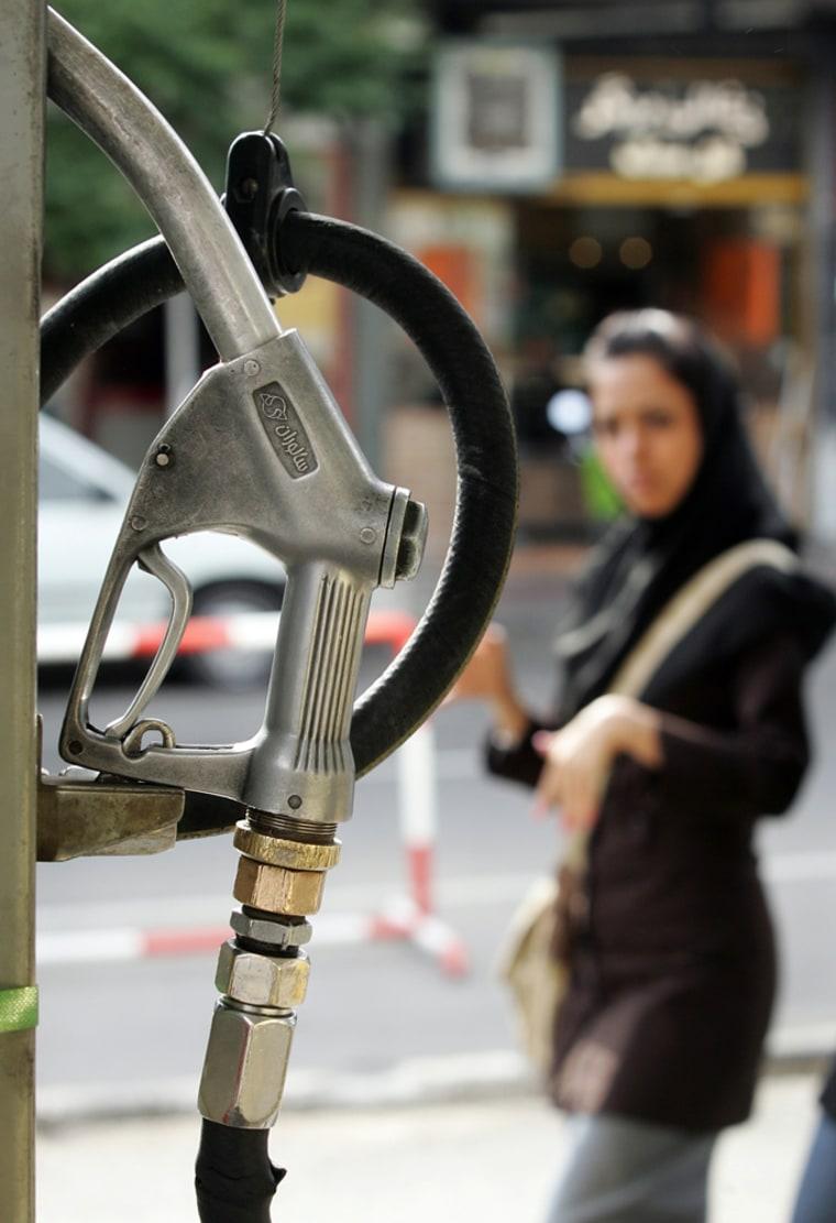 An Iranian woman walks past a gas statio