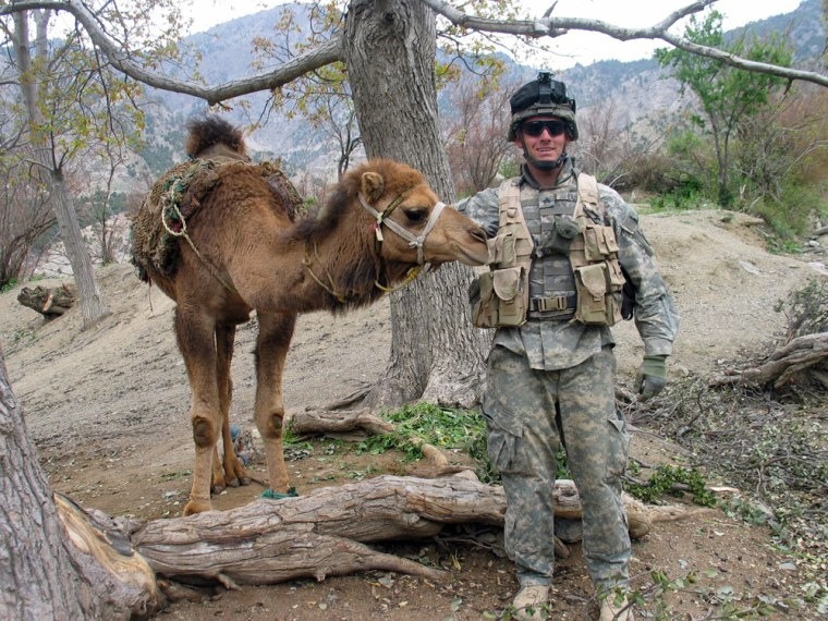 A U.S. Army soldier meets an inhabitant of Jauro, an Afghan village, used to carry firewood cut from local trees down steep hills, on Tuesday.
