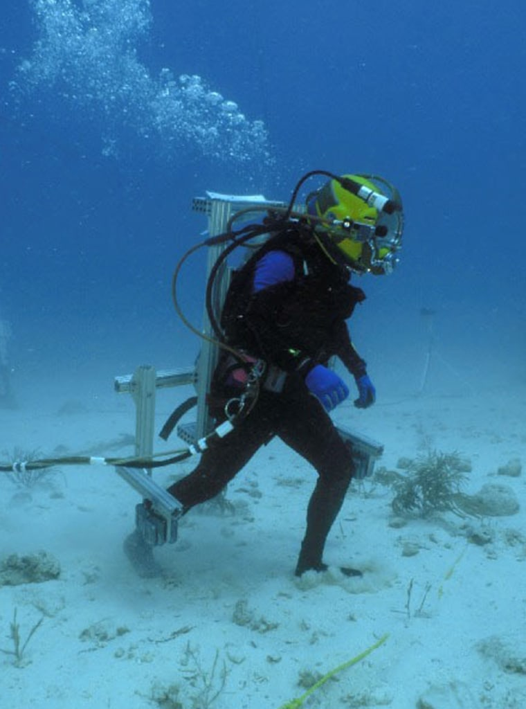 """A NEEMO 9 crewmember conducts a mock """"moonwalk"""" while wearing a harness that changes the center of gravity, giving its wearer thefeeling of one-sixth Earth's gravity — or about the same asthe gravitational pullon the lunar surface."""