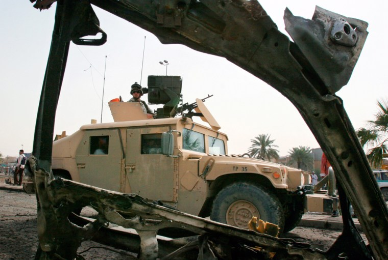 A U.S. Army Humvee passes the wreckage of a car bomb in Baghdad on April 3.
