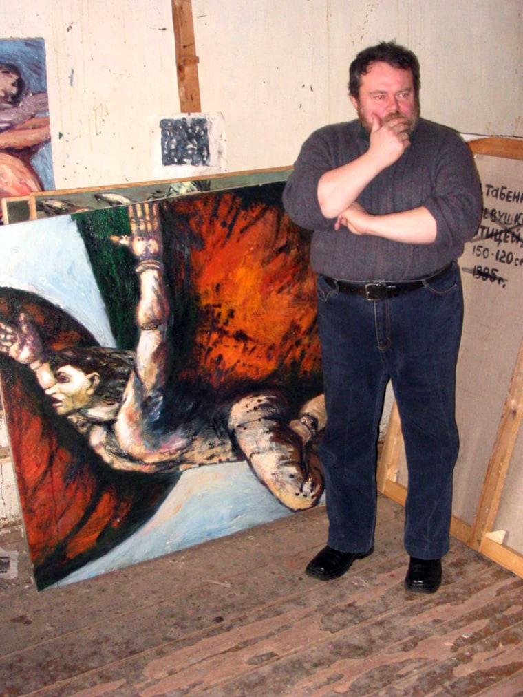 Lev Tabenkin, a painter in Moscow, stands in front of some of his canvasses at a temporary studio. He lost possession of his old studio after the ownership was transferred without his knowledge.