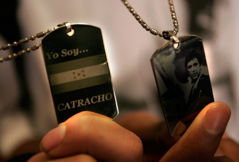 """Students Teofilo Rubi shows his dog tag which says in Spanish, """"I am Honduran"""" (Catracho is slang for a male born in Honduras) and C'Andre Dabney shows off his, whichfeatures a picture of Al Pacino as Scarface."""