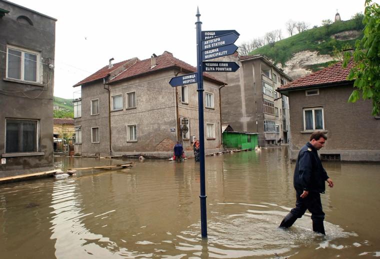 Bulgarian civil defense officer walks on flooded street in town of Nikopol