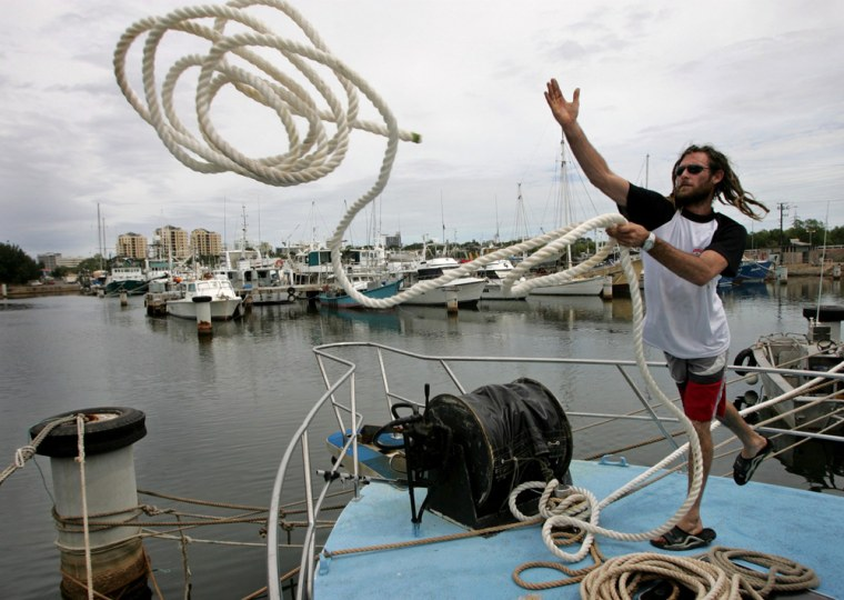 Local fisherman Jennion throws a rope as he ties down his vessel as a massive cyclone approaches Darwin