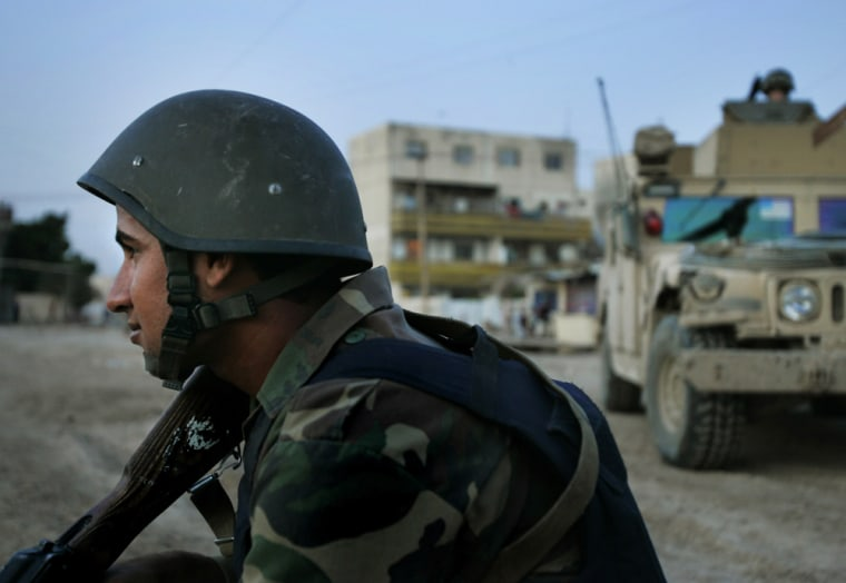 An Iraqicommando patrols Baghdad, Iraq, withU.S. troops on Wednesday. American troops train Iraqi forces while monitoring them to make sure they don't join violent Shiitegroups.